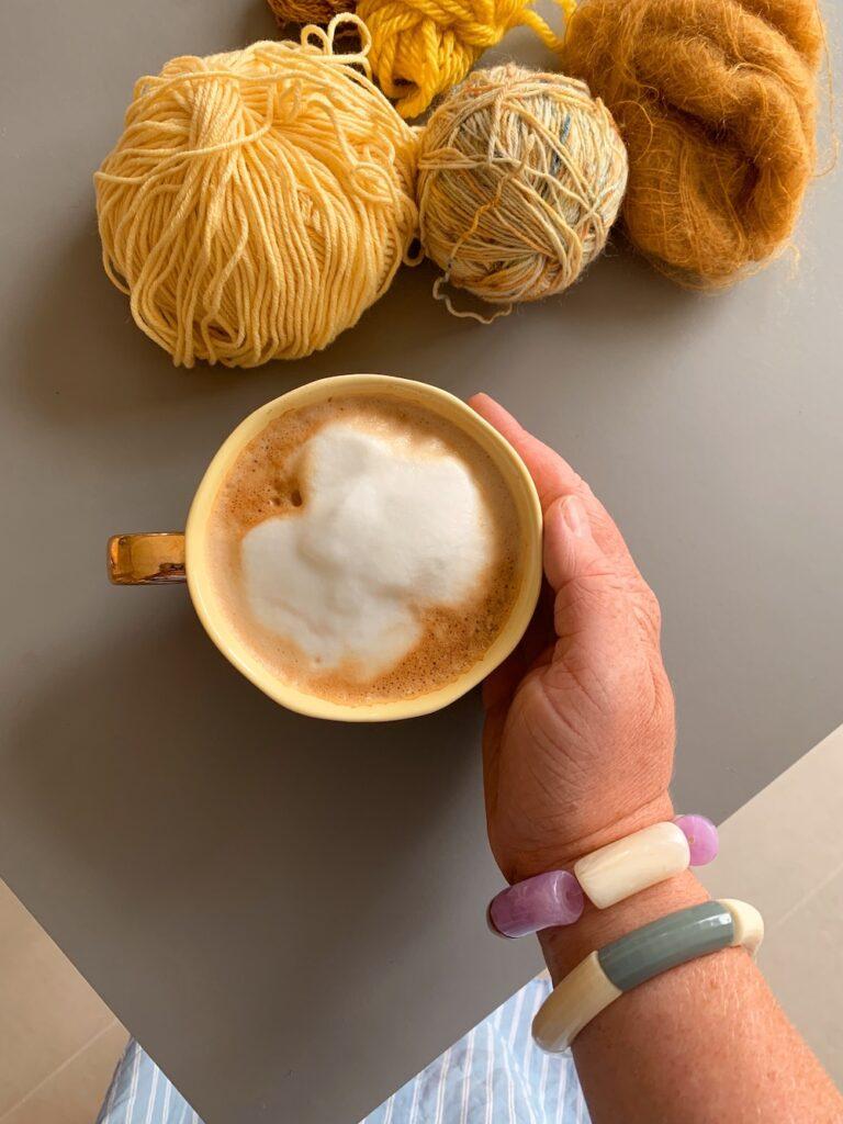 en hånd holder en gul kop med nogle gule restegarner